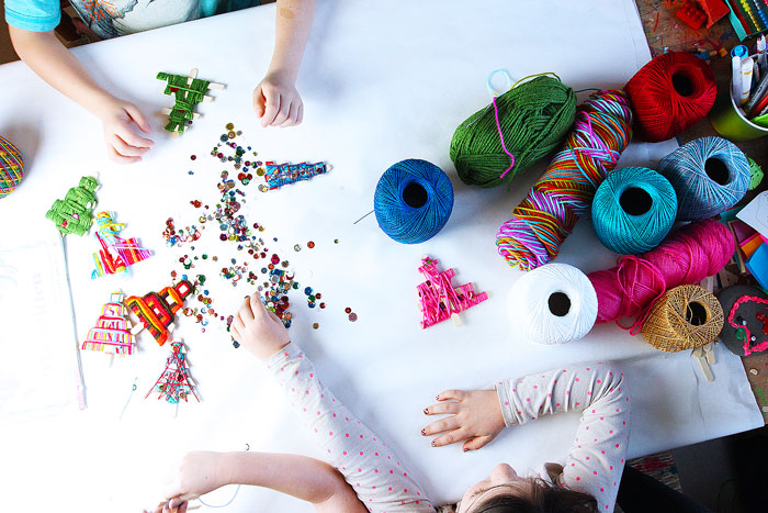 Make homemade Christmas ornaments  from craft sticks and string/yarn. Fun holiday weaving project for kids.